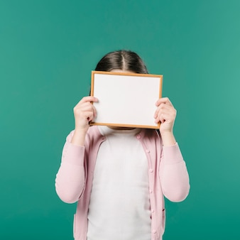 Girl hiding face with picture frame
