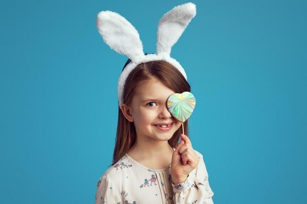 Девушка прячет глаз за печеньем в форме сердца с кроличьими ушками