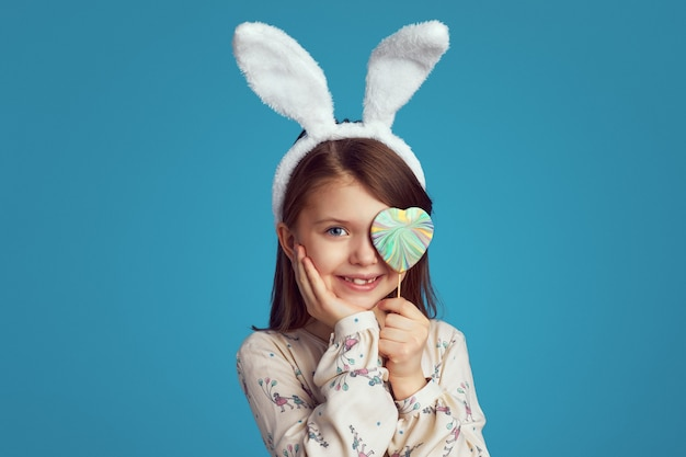 Девушка прячет глаза за печеньем в форме сердца на синей стене