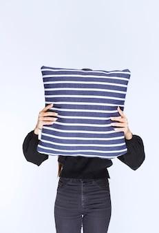 青い縞模様の毛布の後ろに顔を隠している女の子。