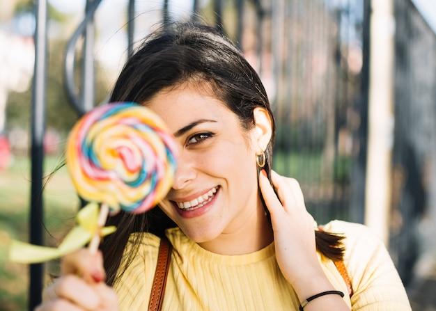 Girl hiding behind lollipop