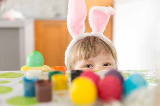 Girl hiding at table with easter eggs