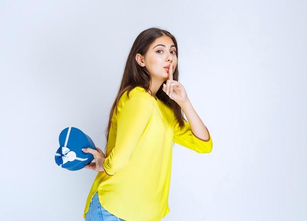 자신의 뒤에 파란 하트 모양 선물 상자를 숨기고 있는 소녀.