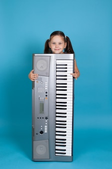 Girl hiding behind a vertical electronic synthesizer and playing its keys