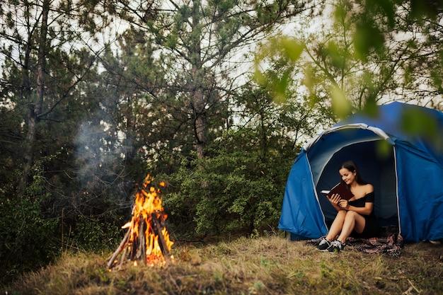 焚き火読書本の近くの森のキャンプテントで女の子ハイカー
