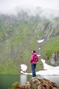 Девушка туристы, стоя на краю скалистого утеса