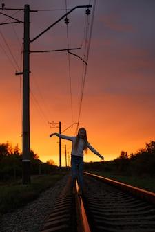 夕日の光の中で鉄道に立っている女の子のハイカー
