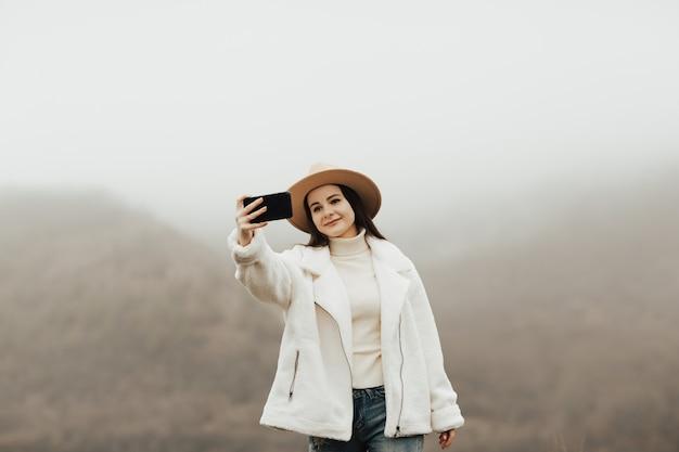 휴대 전화를 사용하여 자연의 아름다운 풍경의 배경에 셀카를 복용 소녀 등산객.