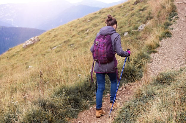 Girl hiker walking along the trail at the mountains dolomites, italy