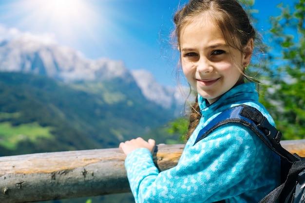알프스 산맥 오스트리아에서 아름다운 여름날에 하이킹하는 소녀, 바위에 쉬고 산봉우리에 대한 놀라운 전망에 감탄하십시오. 아이들과 함께하는 활동적인 가족 휴가 레저. 야외 활동과 건강한 활동