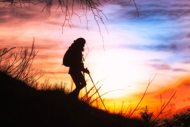 Girl hiking in silhouette downhill