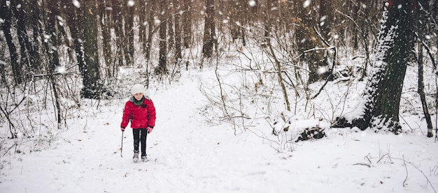 Girl hiking in white winter forest