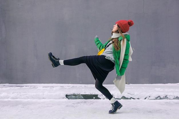 笑ったり笑ったり、街を散歩したり、明るい服を着た女の子のヒップスター。赤いニット帽、緑のジャケット、灰色のスカーフ、灰色の壁の壁に黄色のバッグの若い幸せな女性。女性のファッション。