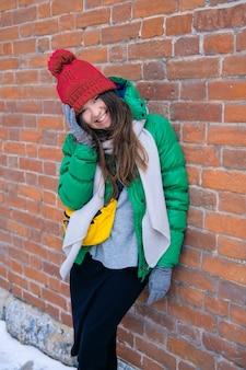 レンガの壁に向かって笑って笑って明るい服を着た女の子のヒップスター。赤いニット帽、緑のジャケット、灰色のスカーフ、黄色の小さなバッグの若い幸せな女性。女性のファッション。