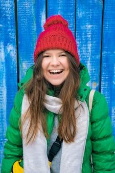 木の板の壁で笑って笑って明るい服を着た女の子のヒップスター。赤いニット帽、緑のジャケット、灰色のスカーフ、黄色のバッグの若い幸せな女性。女性のファッション。秋、春のトレンド