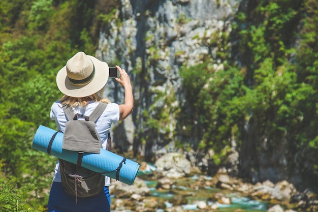 Girl hipster traveler takes pictures of nature on the background of mountains tourist traveler on background.