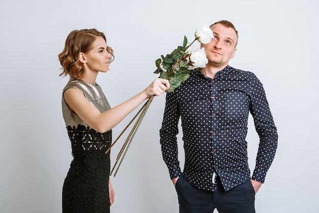 The girl hits her boyfriend on the head with the roses given to her.