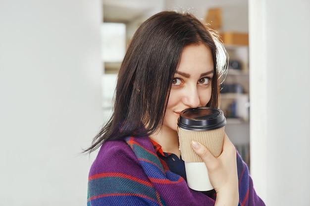 Девушка держит чашку для горячего напитка. она в зимней одежде