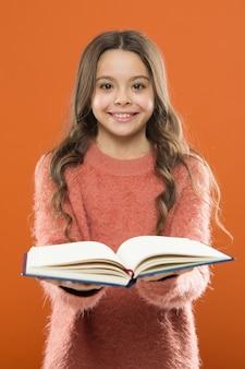 女の子はオレンジ色の背景の上の本を読んだ物語を保持します。子供は本を読むのを楽しんでいます。書店のコンセプト。読むことができる素晴らしい無料の子供向けの本。子供のための読書練習。児童文学。