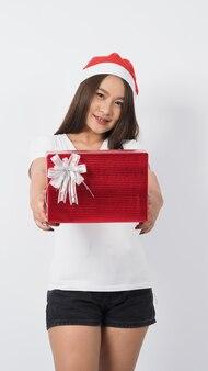 Девушка держит подарочную коробку, делает селфи или видео онлайн с рождественским украшением. азиатская тайская девушка-подросток делает онлайн-селфи, чтобы отпраздновать праздничный сезон со своей подругой в красной подарочной коробке. студийный снимок.