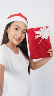 Девушка держит подарочную коробку, сделайте селфи или видео онлайн с рождественским украшением реквизита азиатского тайского подростка