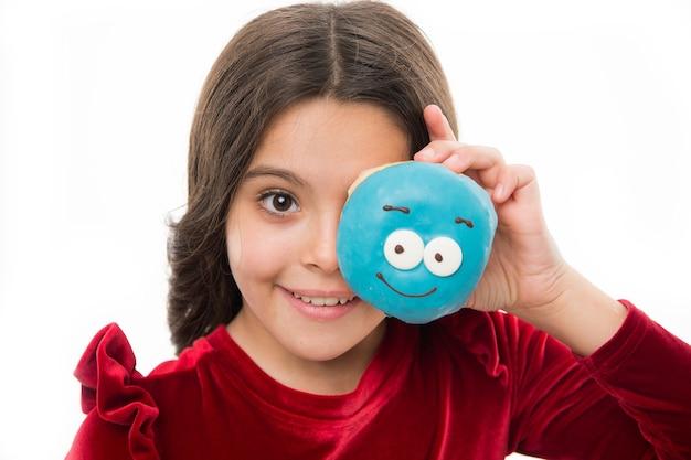 소녀는 흰색 배경에 유약을 바른 귀여운 도넛을 들고 있습니다. 아이 웃는 소녀 도넛을 물 준비가. 과자 가게와 베이커리 컨셉입니다. 구운 도넛을 좋아하는 아이들. 주문한 도넛에 신선한 저항을 할 수 있습니까?