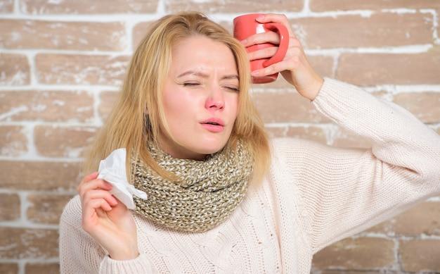 소녀는 차 머그와 티슈를 잡고 있습니다. 콧물 및 기타 감기 증상. 감기에서 빠른 회복을 위해 중요한 수분을 충분히 섭취하십시오. 더 많은 액체를 마시고 감기를 없애십시오. 감기 및 독감 치료제.