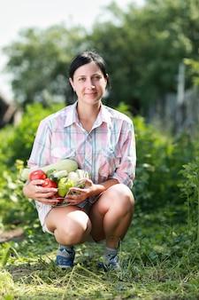 庭で収穫野菜のバスケットを持っている女の子