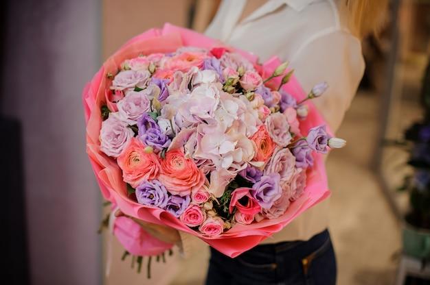 Девушка держит красивый букет разных оттенков розового цвета цветов