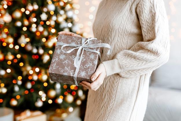 クリスマスプレゼントのクローズアップで美しい箱を保持している女の子