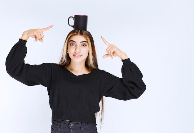 Девушка держит кружку черного кофе у ее головы и чувствует удовлетворение. фото высокого качества