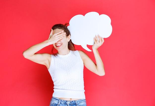 空白の雲の形のアイデアボードを保持し、疲れ果てているように見える女の子。