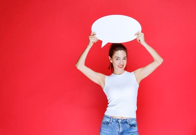 ゲーム用の空白の卵形のアイデアボードを保持している女の子。