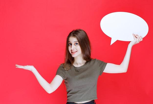 空白の卵形情報ボードを保持し、何かを指している女の子。