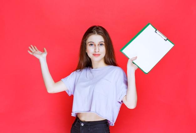 空白のレポートシートを持って、同僚を指さしている女の子。
