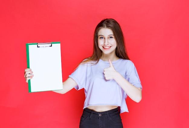 空白のレポートシートを保持し、楽しみのサインを示している女の子。