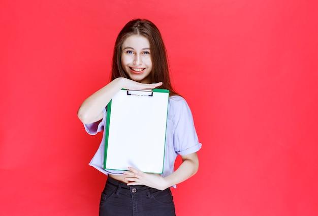 空白のレポートシートを保持している女の子。