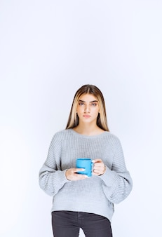 Девушка держит синюю кружку кофе и продвигает ее.