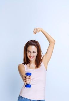 青いダンベルを持って拳を見せている女の子。