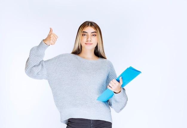 Девушка держит синюю папку и чувствует себя успешным. Premium Фотографии
