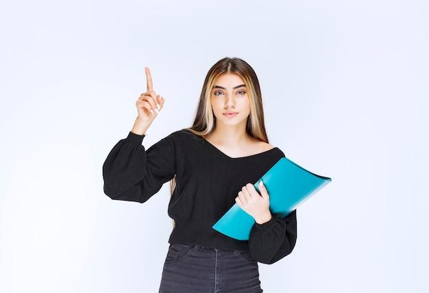 青いフォルダーを保持し、注意のために手を上げている女の子。高品質の写真