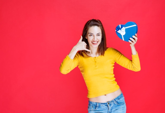 Девушка держит подарочную коробку в форме синего сердца и просит позвонить