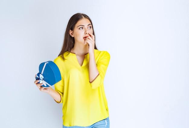 青いハート型のギフトボックスを持って、考えたり、ためらったりしている女の子。