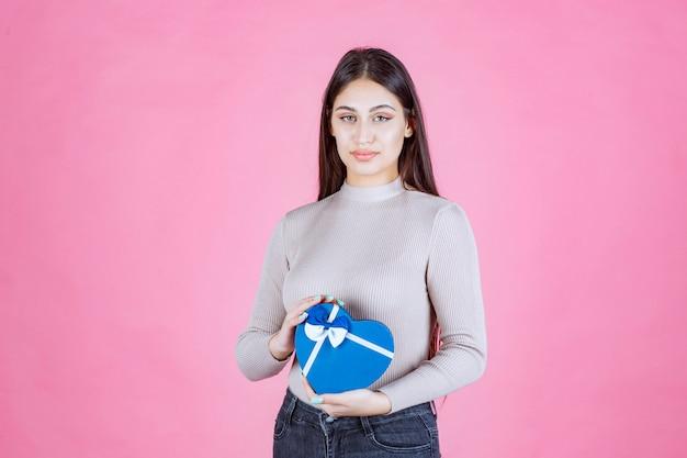 青いハート型のギフトボックスを持って、それを示す女の子