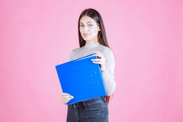 青いプロジェクトフォルダを保持し、成功して幸せそうに見える女の子