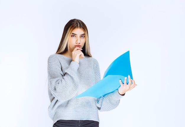 Девушка держит голубую папку отчета и мышления.