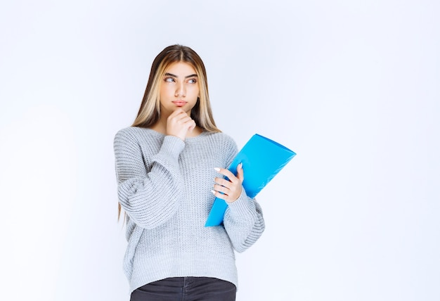파란색 보고서 폴더를 들고 생각하는 소녀.