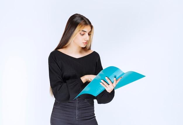 青いレポートフォルダを保持している女の子。高品質の写真