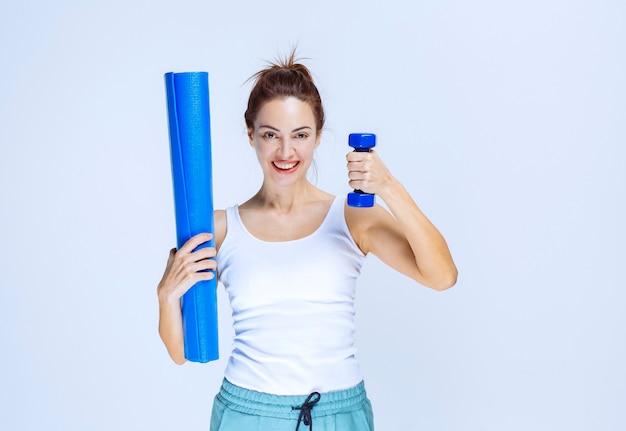 青いロールヨガマットと軽いダンベルを持っている女の子。