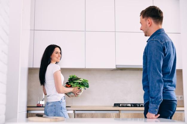 台所で夫と一緒に野菜のボウルを持って、夕食の準備をしている女の子。